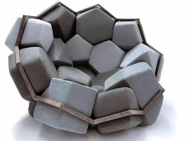 """受自然水晶的启发,设计工作室""""CTRLZAK""""与设计师Davide Barzaghi合作创作了扶手椅""""水晶"""",由简单的材料,铝,泡沫和木头制成。这张水晶创意椅子的构造框架是由相互连接的五边形和六角形结构组成的,里面装满了十六种不同形状的泡沫材料。这个水晶造型让人联想起一个巢,它提供了不可替代的舒适感。它的结构是可变的,每个垫子都可以很容易地从木架上拆卸下来,作为额外的座位使用。垫子颜色变化,从蓝色到深灰色,静谧深沉。通过上面的解说,似乎这把椅子比较高大上的,"""